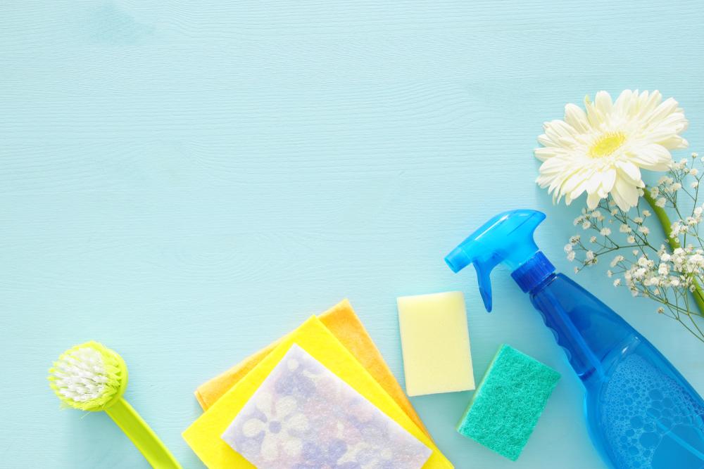Productos de limpieza y desinfección del hogar en fondo azul cielo.